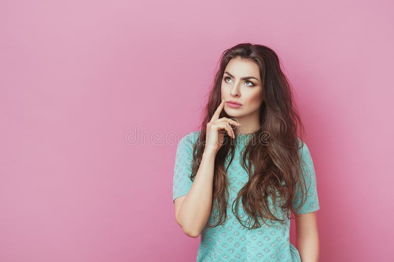 Stående av det attraktiva fundersamma unga kvinnliga hållande pekfingret som upp bort ser med slugt leende Nätt flicka som har de arkivfoton