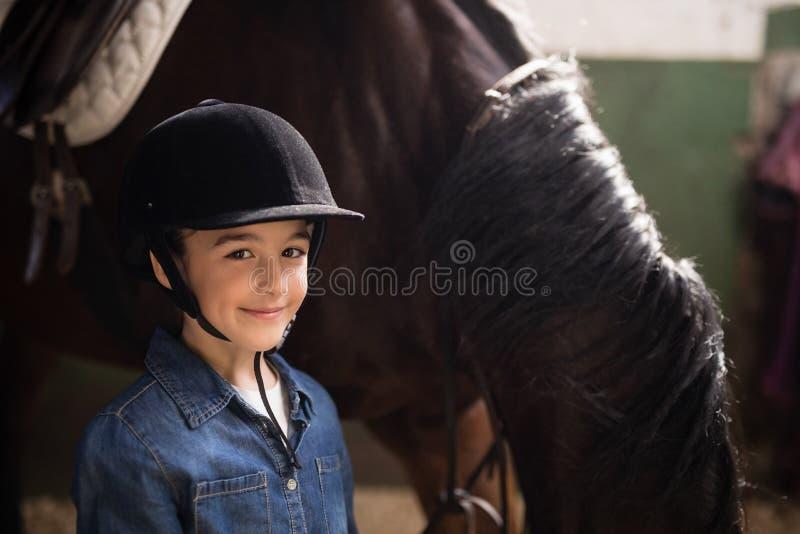 Stående av det bärande hjälmanseendet för flicka vid hästen royaltyfri fotografi
