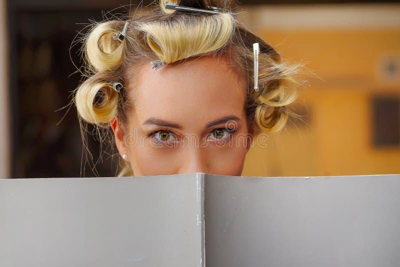 Stående av det blonda kvinnanederlaget bak en bok med hårrullar i huvudet, i en bakgrund för hårsalong arkivfoto