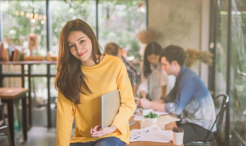 Stående av det coworking kontoret för asiatiskt kvinnligt funktionsdugligt lag, le av lycklig beautif ul-kvinna i modernt kontor arkivfoto