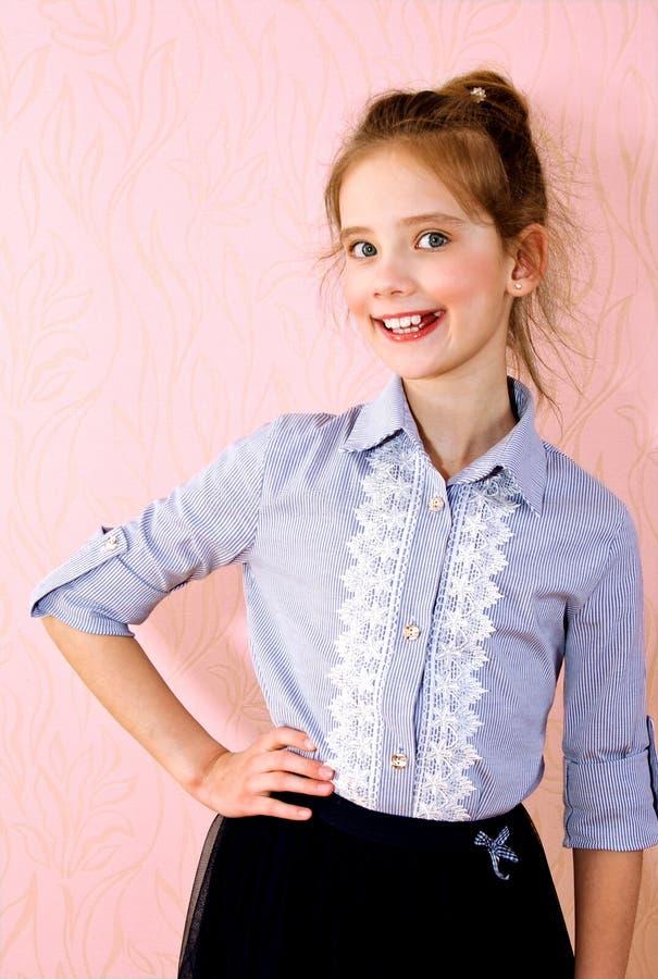 Stående av det förtjusande le liten flickaskolflickabarnet arkivfoto