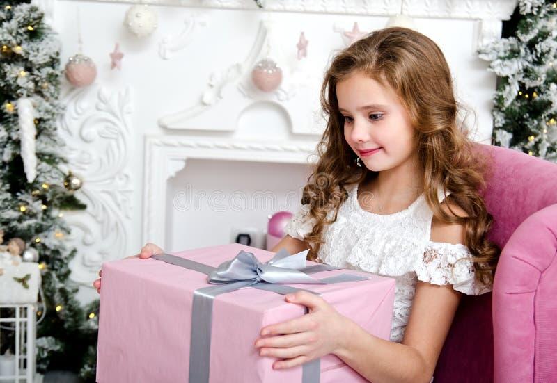 Stående av det förtjusande lyckliga le liten flickabarnet i prinsessaklänningen som sitter i stolen med gåvaasken nära granträd royaltyfria foton