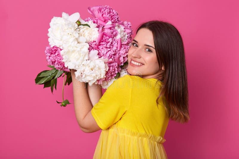 Stående av det gladlynta lyckliga gulliga modellanseendet som isoleras över rosa bakgrund i studion som nästan luktar och sätter  royaltyfri fotografi