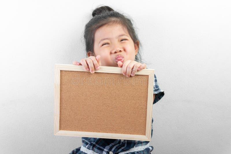 Stående av det gulliga lilla asiatiska tomma kortet för flicka och för innehav royaltyfri foto