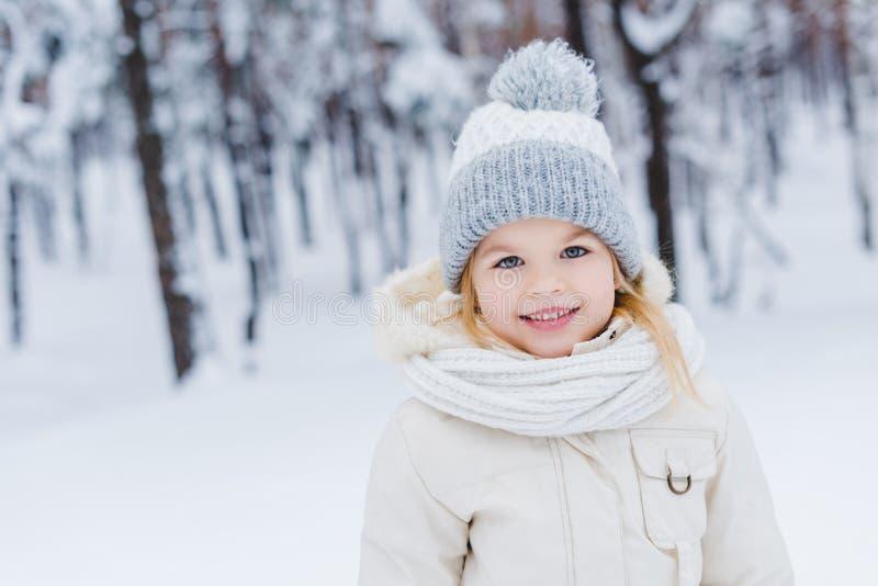 stående av det gulliga lilla barnet i hatt och halsduk som ler på kameran royaltyfria foton