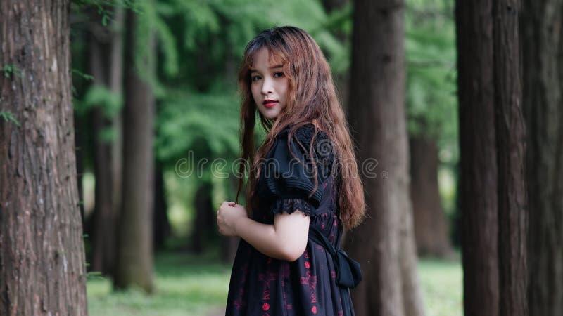 Stående av det härliga asiatiska kvinnaanseendet i sommarskogen, kinesisk flicka i den svarta klänningen för tappning som ser kam arkivbild