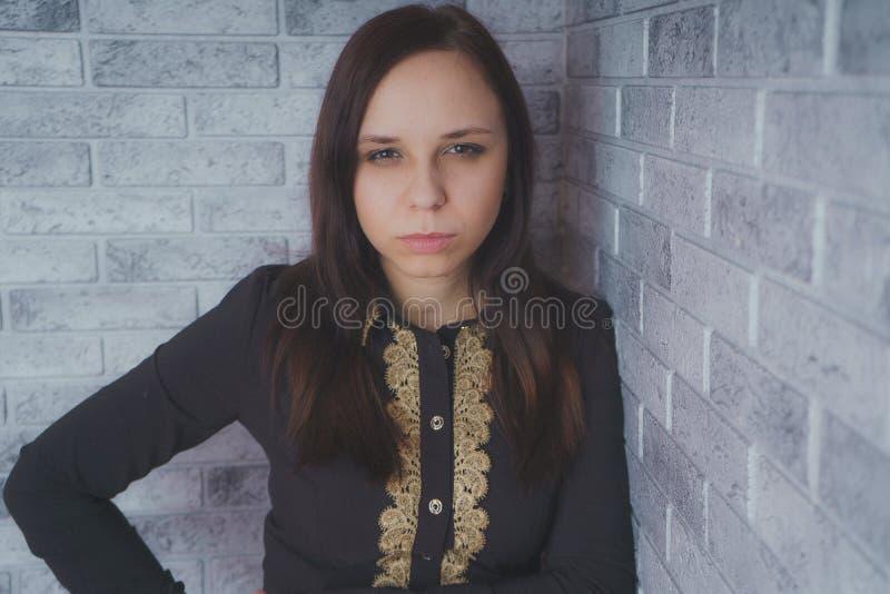 Stående av det härliga lyckaanseendet för ung kvinna på grå bakgrund för tegelsten för vägg för cementtexturgrunge arkivfoto