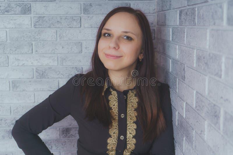 Stående av det härliga lyckaanseendet för ung kvinna på grå bakgrund för tegelsten för vägg för cementtexturgrunge fotografering för bildbyråer