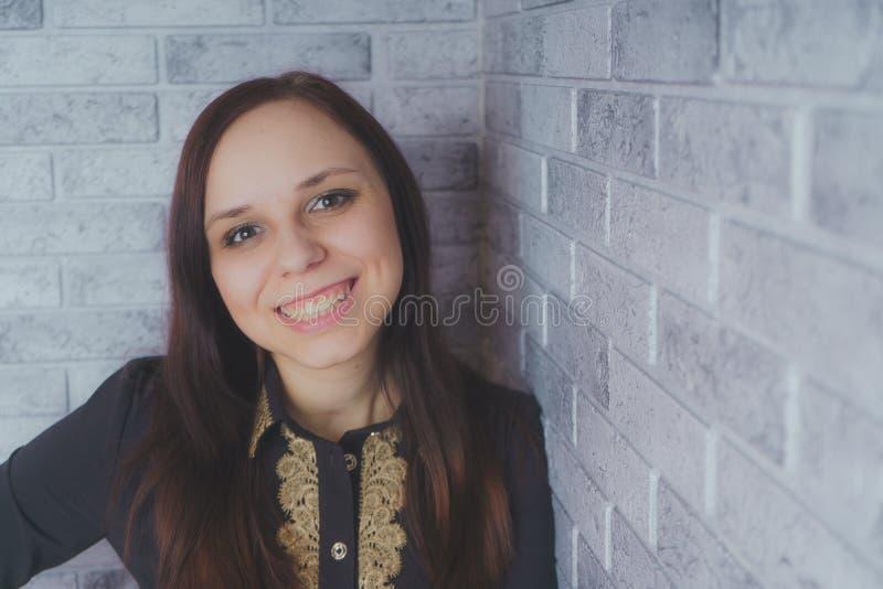 Stående av det härliga lyckaanseendet för ung kvinna på grå bakgrund för tegelsten för vägg för cementtexturgrunge arkivbild