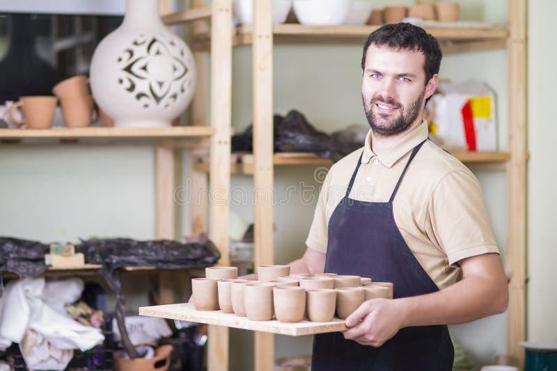 Stående av det hållande magasinet för yrkesmässig manlig Ceramist med Clay Cups royaltyfria foton