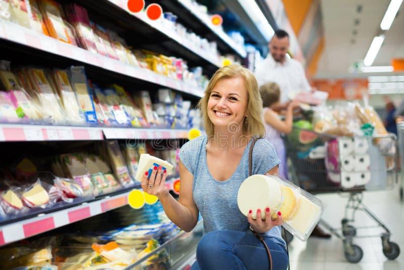 Stående av det hållande sortimentet för kvinna av ost i speceriaffär royaltyfria bilder