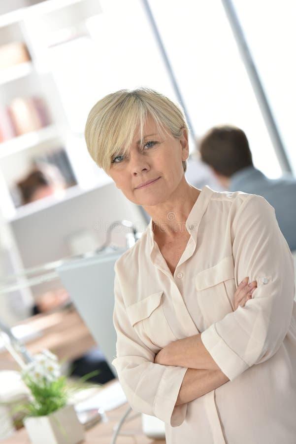 Stående av det höga affärskvinnaanseendet på kontoret arkivbild