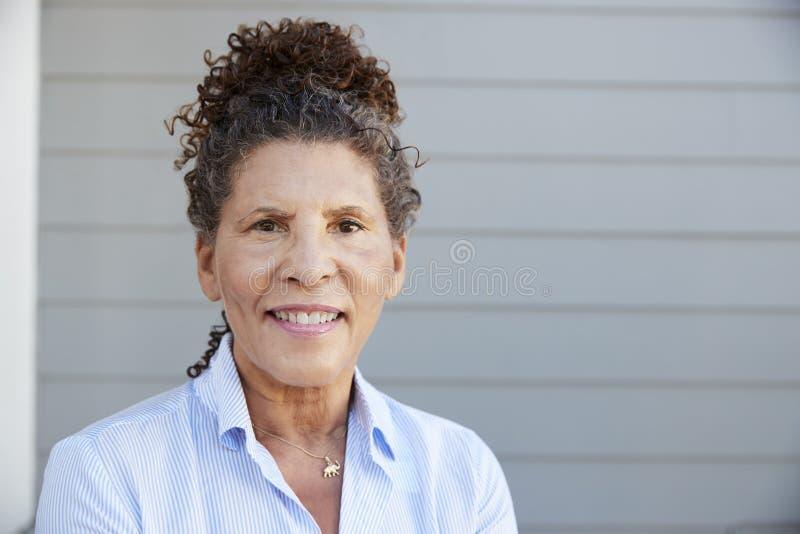 Stående av det höga kvinnaanseendet utanför Grey Clapboard House arkivfoto