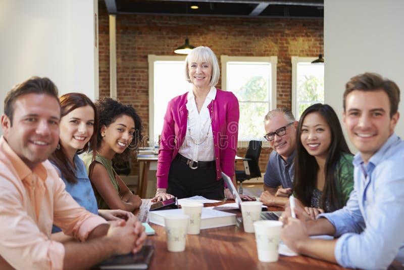 Stående av det höga kvinnliga framstickandet With Team In Meeting royaltyfria foton