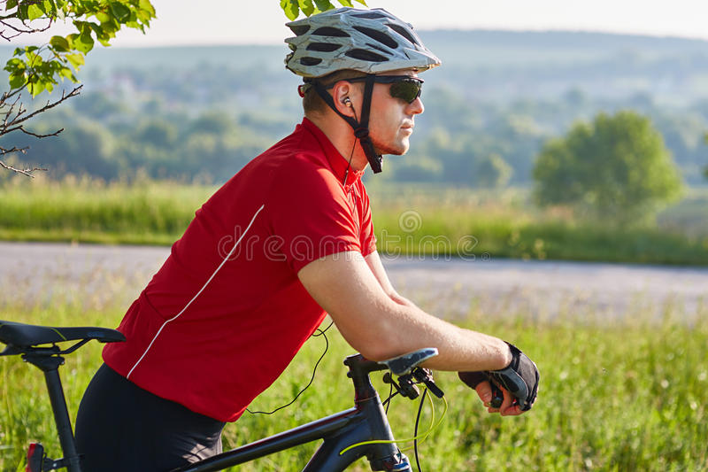 Stående av det idrotts- mananseendet med mountainbiket mot vägen i bygden royaltyfri fotografi