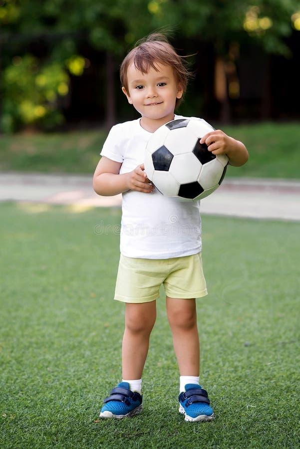 Stående av det lilla litet barnbarnanseendet i det gröna fotbollfältet som rymmer fotbollbollen Le den lilla fotbollsspelaren på  royaltyfri foto