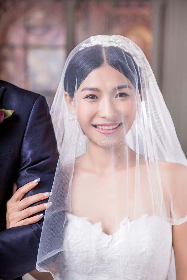 Stående av det lyckliga brudanseendet med brudgummen i kyrka arkivbild