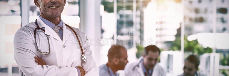 Stående av det lyckliga doktorsanseendet med korsade armar, medan hans kollegor arbetar royaltyfri fotografi