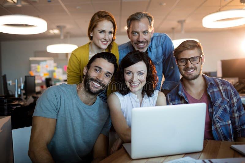 Stående av det lyckliga idérika affärslaget som arbetar på bärbara datorn royaltyfri foto