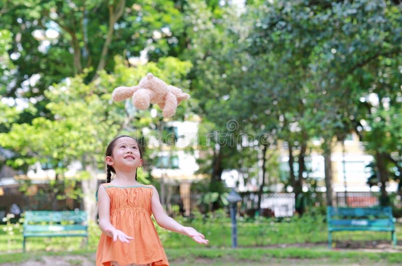 Stående av det lyckliga lilla asiatiska barnet i grön trädgård med att kasta upp dockan för nallebjörn som svävar på luft Le unge arkivfoton