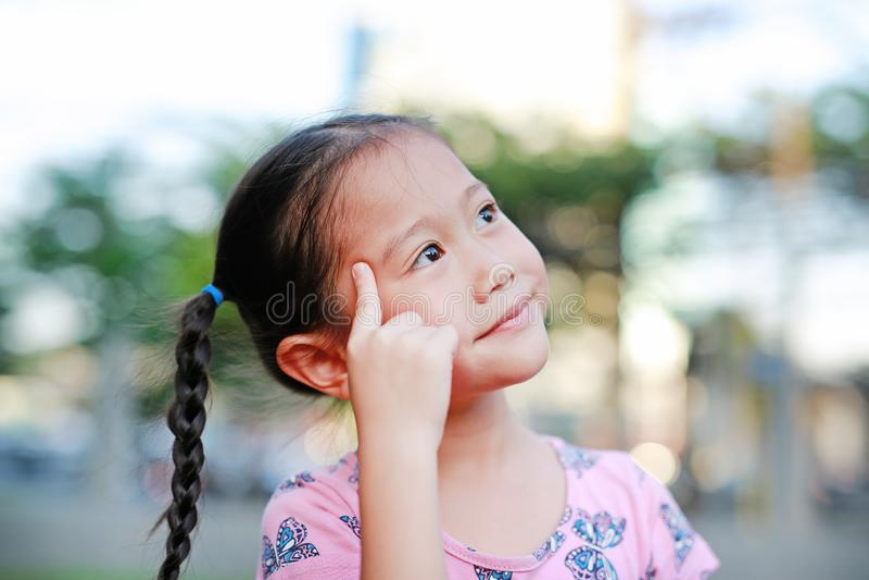 Stående av det lyckliga lilla asiatiska barnet i trädgård med att tänka och att se upp Närbild som ler på ungeflickan med pekfing royaltyfria foton