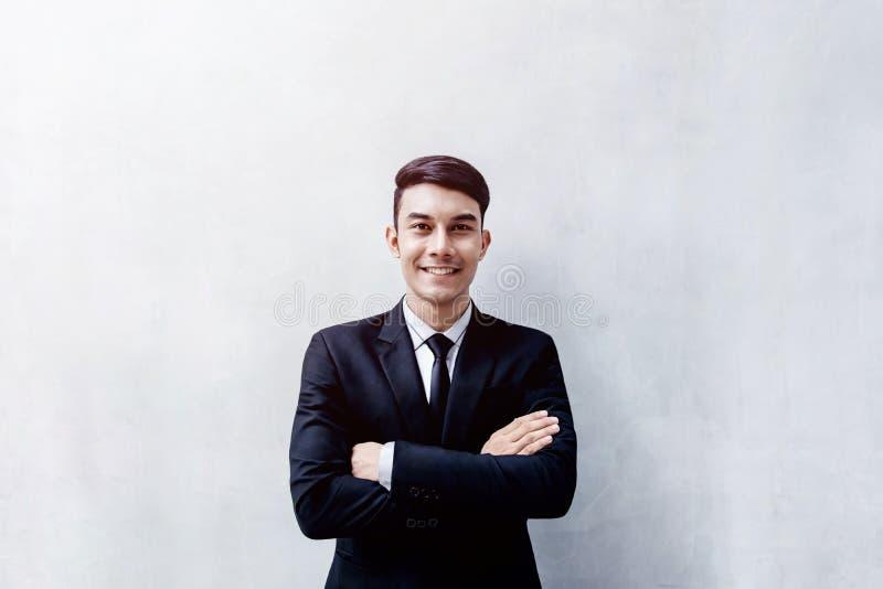 Stående av det lyckliga unga affärsmananseendet på väggen, Smilin arkivbilder