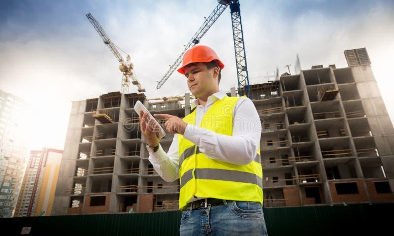 Stående av det manliga anseendet för konstruktionstekniker på byggnadsplats och att använda den digitala minnestavlan fotografering för bildbyråer