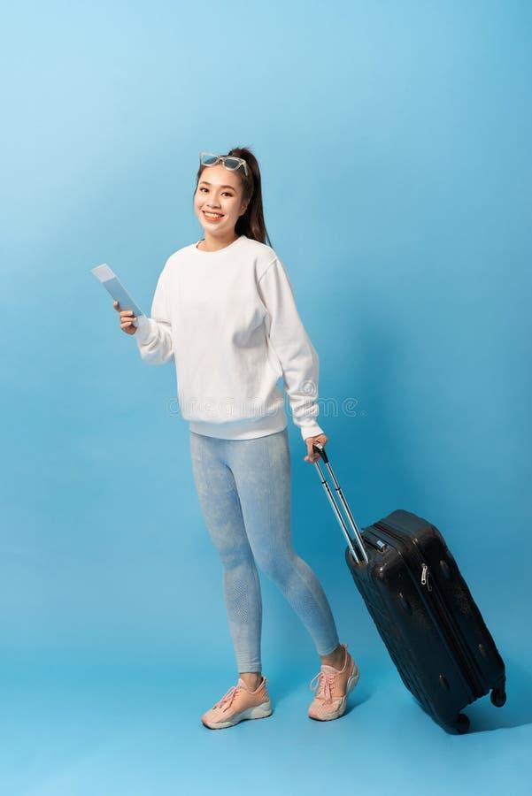 Stående av det moderiktiga ung flickaanseendet med resväskan och rymmapasset med biljetter, över blå bakgrund arkivfoto