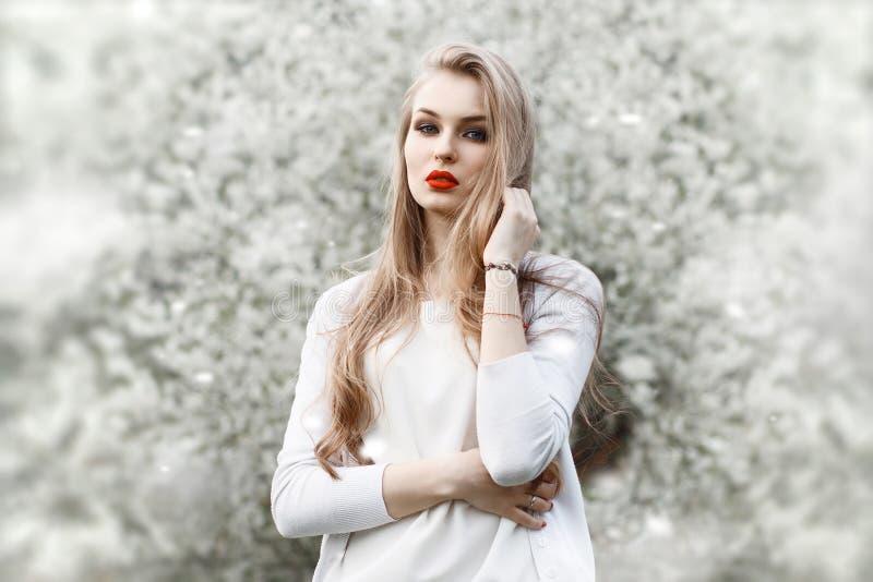 Stående av det near blomstra trädet för ung kvinna röda kanter royaltyfri foto