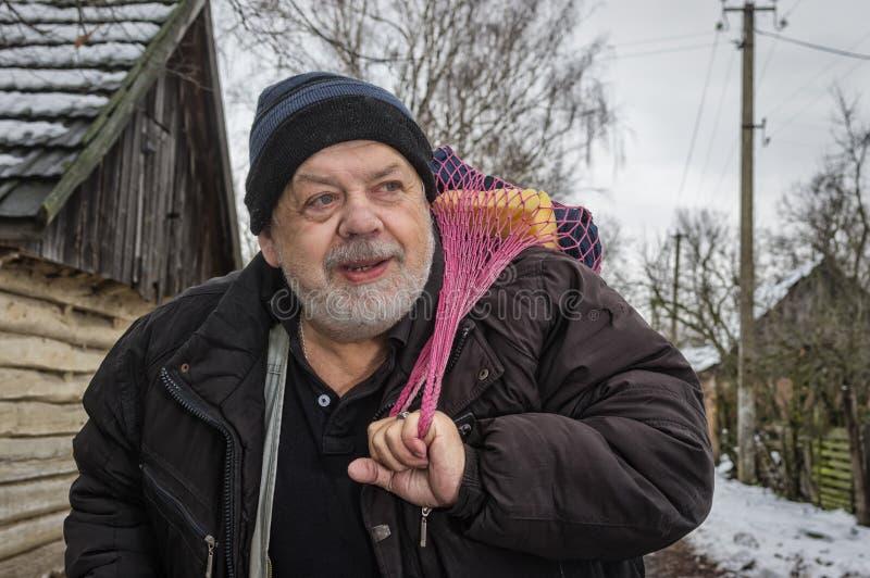 Stående av det positiva ukrainska bondaktiga anseendet på en gata för lantlig by och tarad-påsen med hushållsaker royaltyfri bild