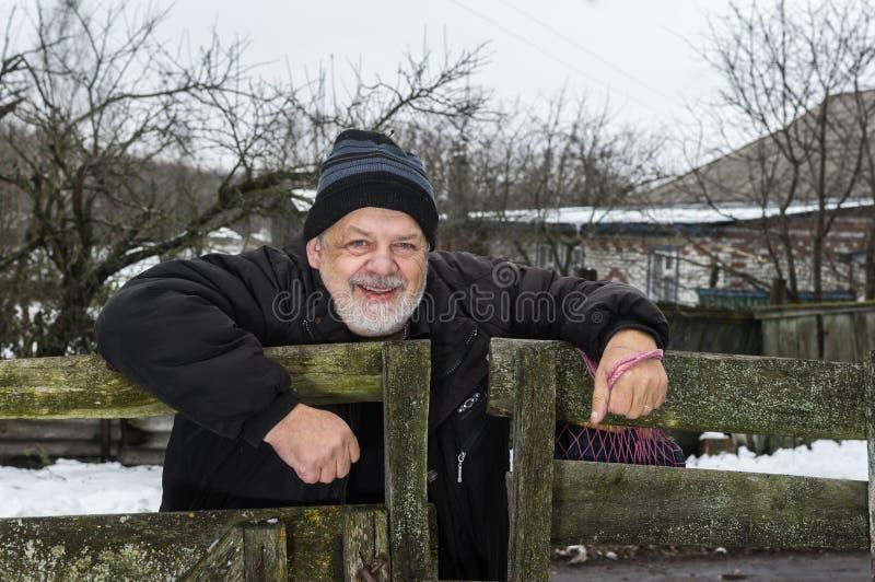 Stående av det positiva ukrainska gamal mananseendet på hans staket i lantlig ukrainsk by arkivbild
