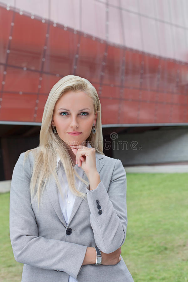 Stående av det säkra affärskvinnaanseendet med handen på hakan mot kontorsbyggnad arkivfoton