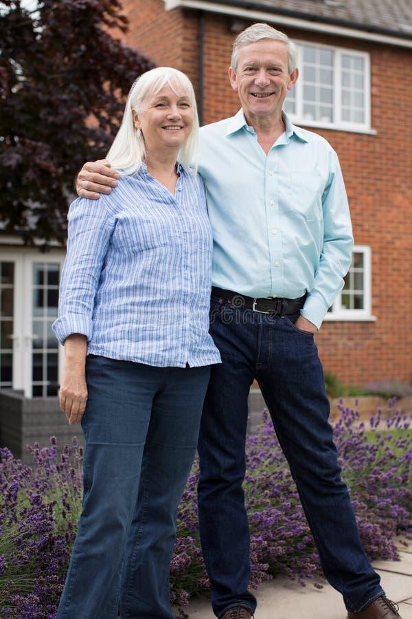 Stående av det stående yttersidahemmet för pensionerade par royaltyfria foton
