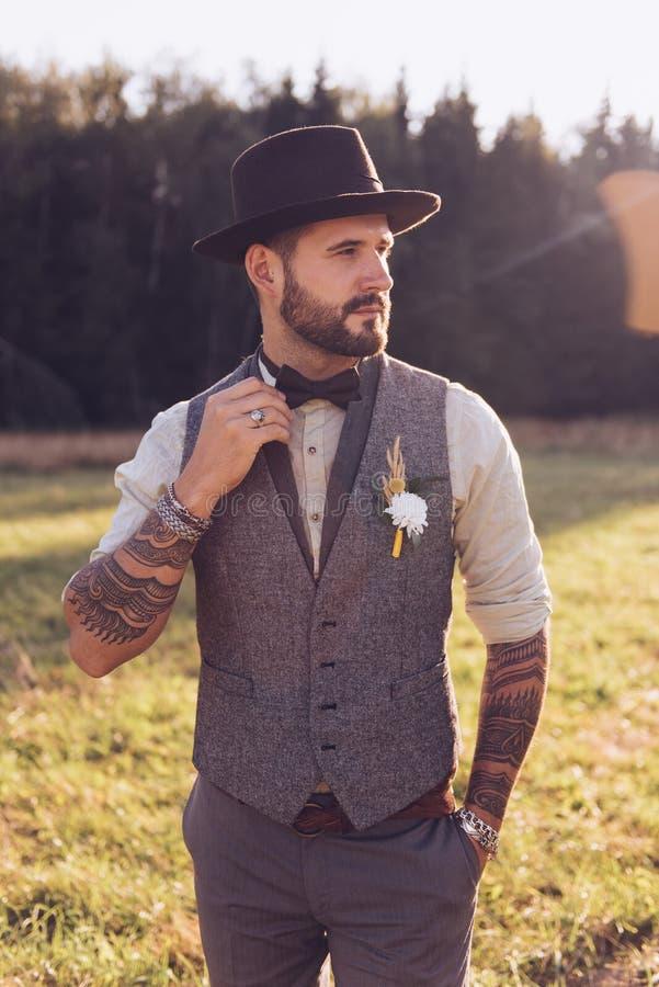 Stående av det stilfulla skägget, man med tatueringar på hans armar bröllop för stående för prydnad för brudgum för bakgrundsbrud royaltyfria bilder