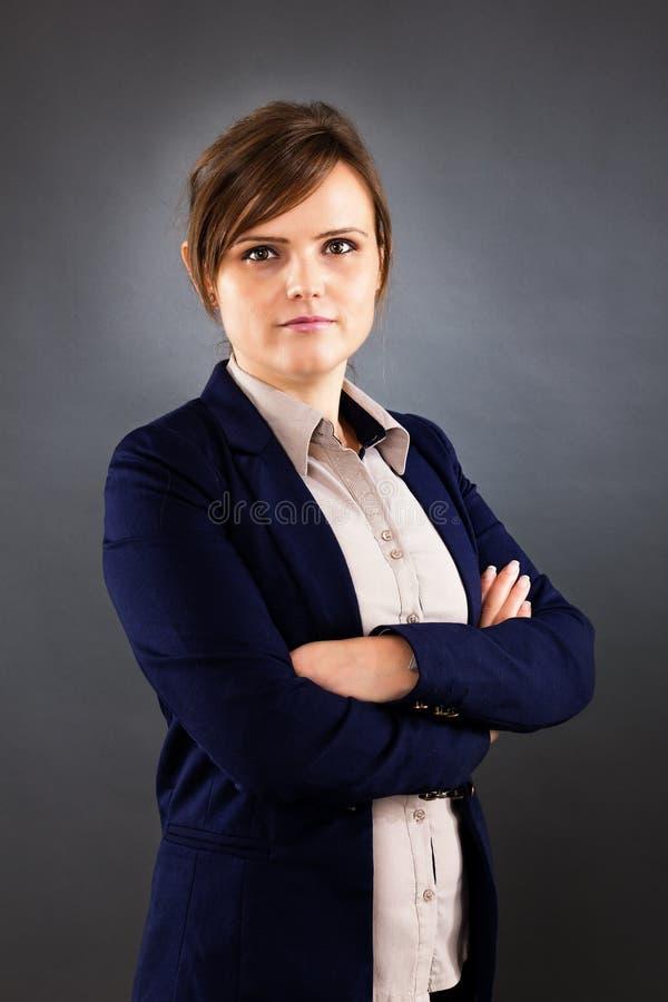Stående av det unga anseendet för affärskvinna med korsade armar arkivbild