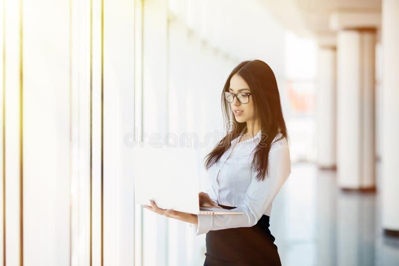 Stående av det unga anseendet för bärbar dator för affärskvinna funktionsdugliga hållande mot panorama- fönster med stadssikt royaltyfria bilder