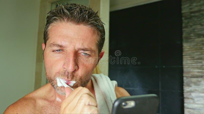 Stående av det unga hemmastadda badrummet för stilig och attraktiv internetknarkareman med handduken på tvättande tänder för skul fotografering för bildbyråer