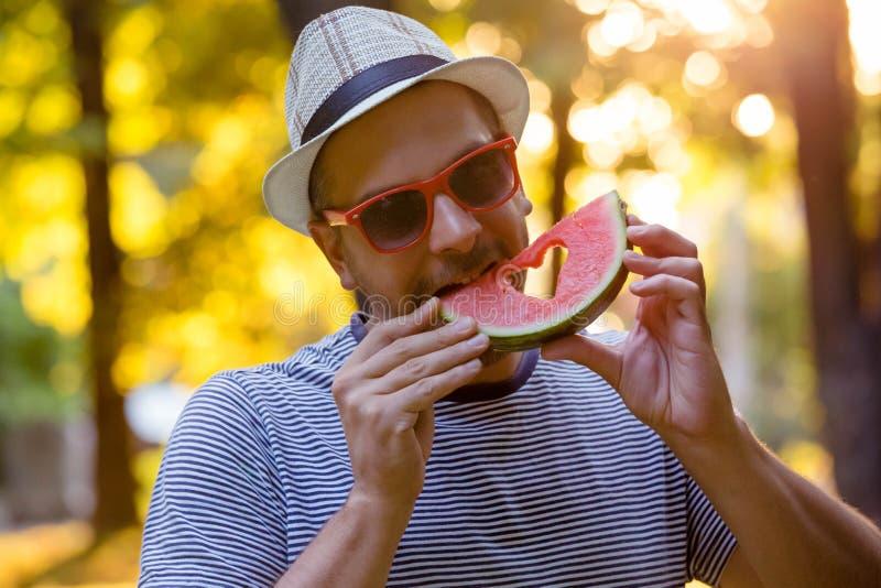 Stående av det unga innehavet och att äta för hipsterman vattenmelonskivan royaltyfri fotografi