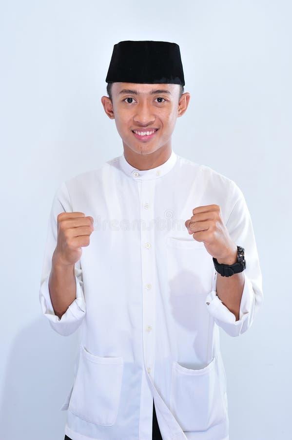 Stående av det unga stiliga asiatiska muslim manleendet som tycker om eiden mubarak fotografering för bildbyråer