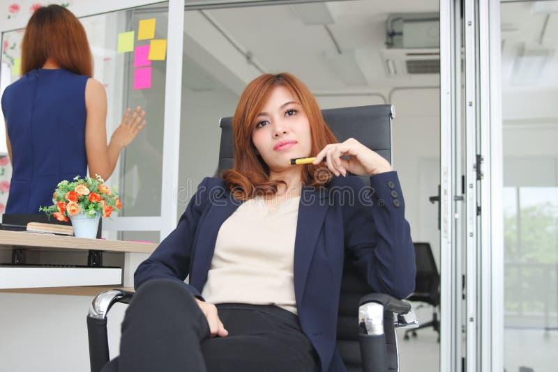 Stående av det ursnygga kvinnliga framstickandet som i regeringsställning sitter på arbetsplatsen arkivfoto