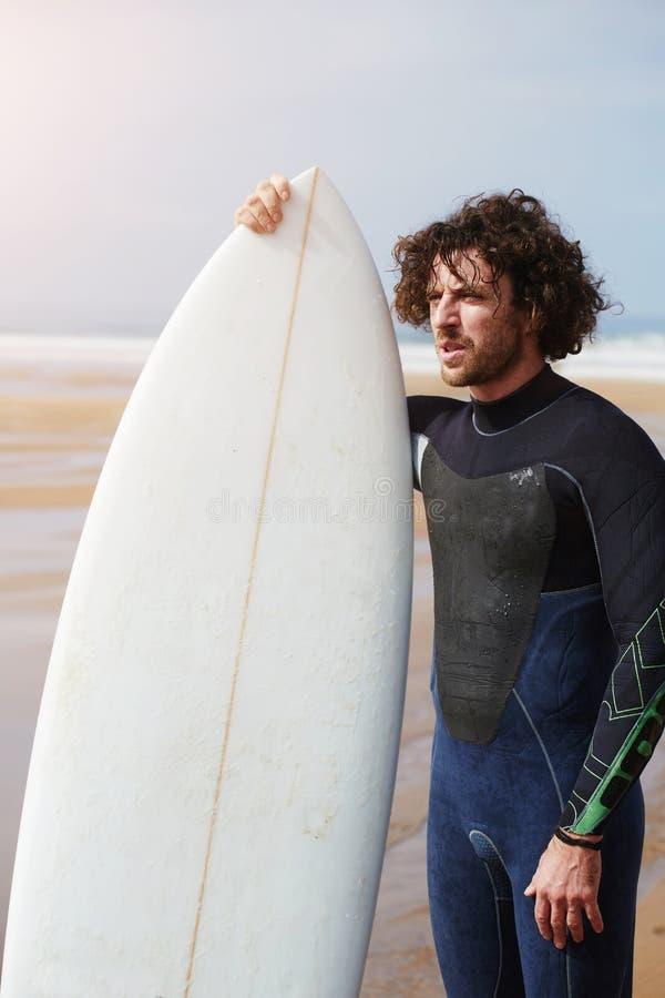 Stående av det yrkesmässiga unga surfareanseendet mot havet som rymmer hans härliga surfingbräda arkivfoto