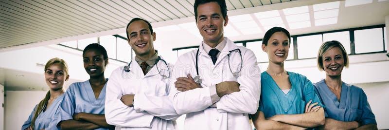 Stående av doktorer och sjuksköterskor med korsade armar fotografering för bildbyråer