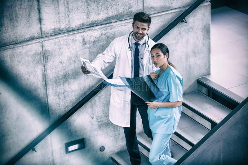 Stående av doktorn och sjuksköterskan som rymmer medicinska rapporter royaltyfria foton