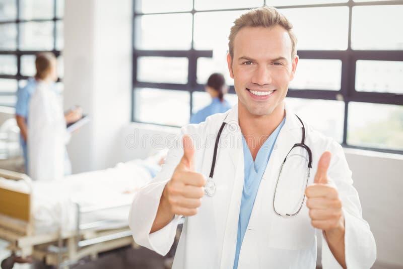 Stående av doktorn som upp ger tummar och att le royaltyfria bilder