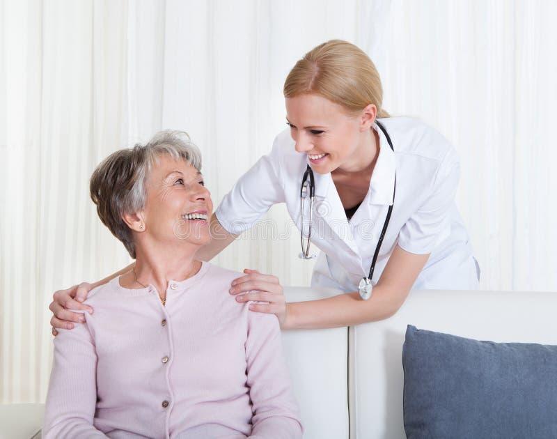 Stående av doktors- och patientsammanträde på soffan royaltyfria bilder