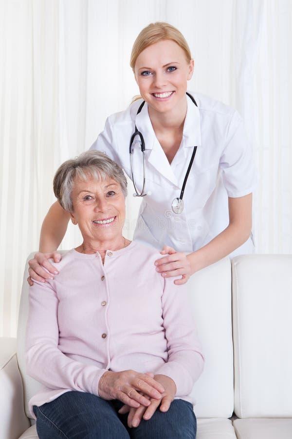 Stående av doktors- och patientsammanträde på soffan royaltyfri bild