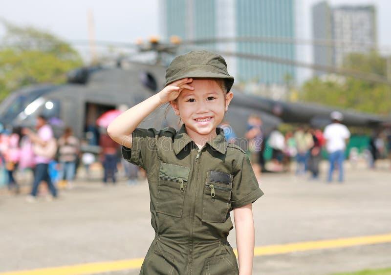 Stående av dräkten för flygvapen för asiatisk barnflicka den bärande pilot- mot suddighetshelikopterbakgrund arkivfoton