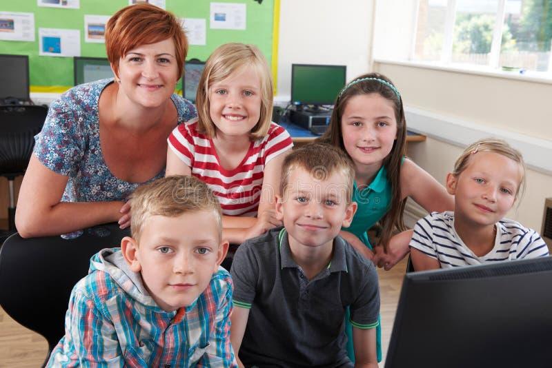 Stående av elementära elever i datorgrupp med läraren fotografering för bildbyråer