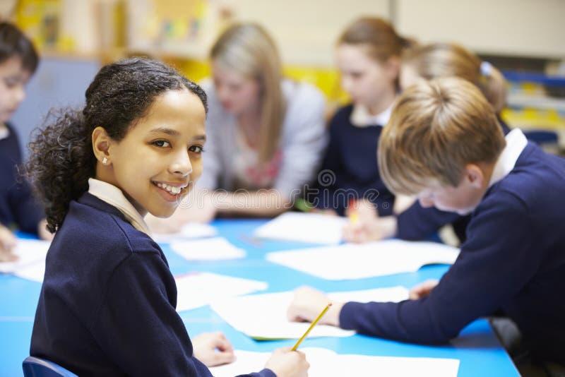 Stående av eleven i klassrum med läraren arkivfoto