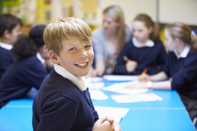 Stående av eleven i klassrum med läraren arkivbilder